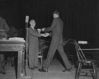 An unidentified Mankato State College student at a presentation ceremony, 1962-05-25.
