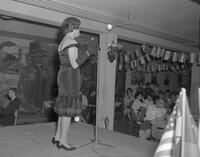 Bonnie Frey entertains with a German song at Language Club floor show at Mankato State College Charity Carnival, 1963-04-05.