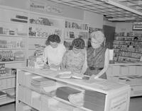 Mrs. Dubke, Wigwam Bookstore Manager at Mankato State College working with Mrs. Turner and another unidentified woman, 1962-06-19.