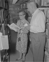 Mrs. Youel and another librarian looking over books from Bookmen's exhibit at Mankato State College, 1962-06-28.