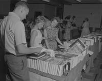 Mankato State College Students looking over books from Bookmen's exhibit, 1962-06-28.
