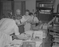Mankato State College Students and Staff looking over books from Bookmen's exhibit, 1962-06-28.