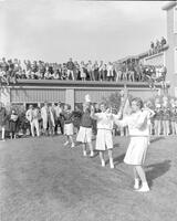 Mankato State College Cheerleaders cheering at homecoming pep rally, 1962-11-09.