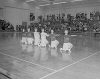 Mankato State College Cheerleaders performing at basketball game against South Dakota University, 1963-02-23.