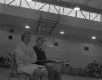 Joan Tubbelsing holding flash cards at a gym meet, Mankato State College, 1963-02-23.