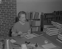 Woman in her office reading a book at Mankato State College, 1963-02-23.