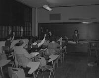 Kenneth Brown and female students at a SNEA meeting, Mankato State College, 1963-03-22.