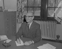 Man sitting at his desk writing at Mankato State College, 1963-03-22.
