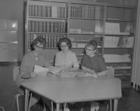Nursing club members looking at journals, Mankato State College, 1963-05-21.