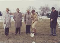 A picture of Mankato State University president, Margaret R. Preska (holding shovel) and Dr. Claire Faust (left of Preska) with three other men during a ground-breaking ceremony for a new steel building being constructed near the Wiecking Center building,