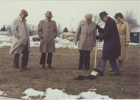 A picture of a man using a shovel to participate in a Mankato State University ground-breaking ceremony for a new steel building near the Wiecking Center building, 1970s.