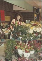 A picture of a Mankato State University student standing next to some plants in the MSU Centennial Student Union, 1980s.