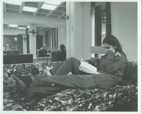 A picture of a female Mankato State University student studying on a couch in the Centennial Student Union, 1970s.