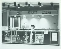 "A picture of two Mankato State University students working at the Centennial Student Union's ""Reservations and Information"" desk, 1970s."