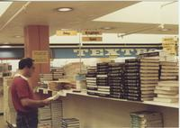 A picture of a Mankato State University student looking at textbooks in the Centennial Student Union bookstore, 1980s.