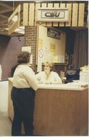 A picture of a woman asking a Mankato State University student worker a question in the Centennial Student Union, 1980s.