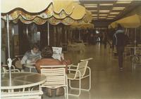 A picture of two Mankato State University students reading the Reporter newspaper in the Centennial Student Union, 1980s.