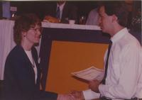 A woman receiving an certificate for participating in the Computer and Information Science fair in the Centennial Student Union Ballroom at Mankato State University, 1991-05-15.