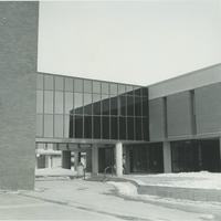 A picture of a Mankato State University student walking from the Wigley Administration Center into the Morris Hall academic building, 1980s.