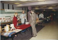 A picture of a man visiting a Soviet Union booth during an event in the Mankato State University Centennial Student Union, 1980s.