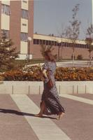 Woman walking by a garden, barefoot, Mankato State College.