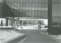 A picture of two Mankato State University students talking to each other underneath the Wigley Administration Center/Morris Hall academic building enclosed walkway, 1970s.