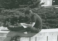 Male art student, sitting cross legged, drawing outside on Mankato State University Campus Mall.