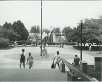 A picture taken from the Armstrong Hall academic building of Mankato State University students walking on the Campus Mall, and relaxing near the university fountain, 1980s.