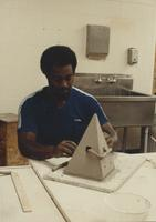Male ceramics student working on slab pyramid design, Mankato State University