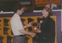 President Margaret R. Preska giving man a plaque during the Computer and Science event in the Centennial Student Union Ballroom at Mankato State University, 1991-05-15.