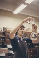 Male chemistry student pouring liquid, Mankato State University