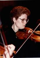 A picture of a Mankato State University Orchestra member playing an instrument during an MSU Concerto Concert, 1987.