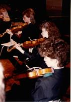 A picture of some Mankato State University orchestra members playing their instruments during a 1987 concerto concert in the Performing Arts Center.
