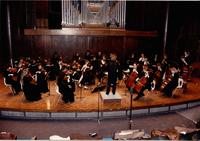 A picture of the Mankato State University orchestra, directed by Emily Freeman Brown (standing with back to camera), performing during a 1987 concerto concert.