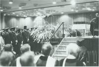 A picture of Mankato State University graduates standing during a 1976 commencement ceremony in the Centennial Student Union Ballroom.