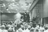 A picture of a recent Mankato State University graduate shaking hands with a man on stage during a 1976 commencement ceremony in the Centennial Student Union Ballroom.