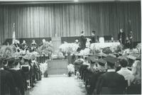 A picture of a Mankato State University graduate accepting his diploma on stage during a 1976 commencement ceremony in the Centennial Student Union Ballroom.