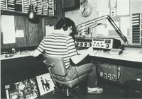 A picture of a Mankato State University student working at the KMSU radio station, 1980s.