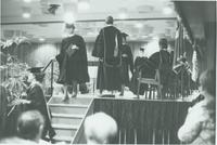 A picture of a recent Mankato State University graduate walking off the stage during a 1976 commencement ceremony in the Centennial Student Union Ballroom.