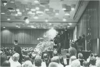 A picture of recent Mankato State University graduates walking off the stage during a 1976 commencement ceremony in the Centennial Student Union Ballroom.