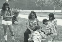 A picture of two women and a man from the Mankato State University Upward Bound program working with three children outside of a university building, 1970s.