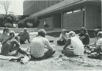 Students sitting outside in a group in the grass by Armstrong hall at Mankato State University