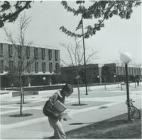 A picture of a Mankato State College student walking off of the Campus Mall toward the MSC Memorial Library, 1970s.