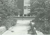 A picture of a Mankato State University student walking on the Campus Mall by the Nelson Hall academic building, 1980s.