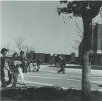 A picture of Mankato State College students walking on the campus mall near Armstrong Hall, the Trafton Science Center, and Nelson Hall,  1970s.