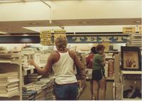 A picture of three Mankato State University students looking at textbooks in the MSU bookstore, 1985.