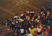 Cheerleaders and spectators on the sideline observing the game at Mankato State University, 1990-09-15.