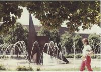 A picture of a Mankato State University student walking by the fountain, 1980s.