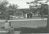 A picture of Mankato State University students around the fountain, Chthonic Sculpture, campus mall and Armstrong Hall academic building, 1980s.