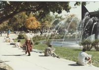 A picture of Mankato State University students gathered around the university fountain and on the Campus Mall near the Armstrong Hall academic building, 1980s.